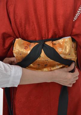 袴の中心を体の中心に合わせて袴を合わす。前紐の帯を羽根の上で人結び。帯の真ん中で交差して前へ出す