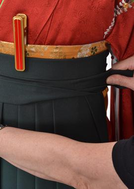 前で袴紐を衿合わせに交差して、下になる方をおり上げる